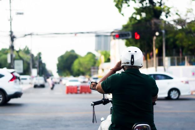 男性は緑色のジャケットと白いヘルメットを着用し、オートバイに乗り、車を停め、信号機を待ちます。