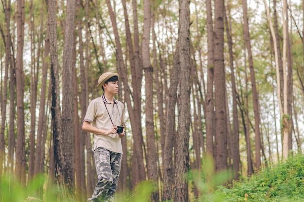 アジア人男性はシャツ、帽子、迷彩パンツを着て歩いて森で写真を撮っている