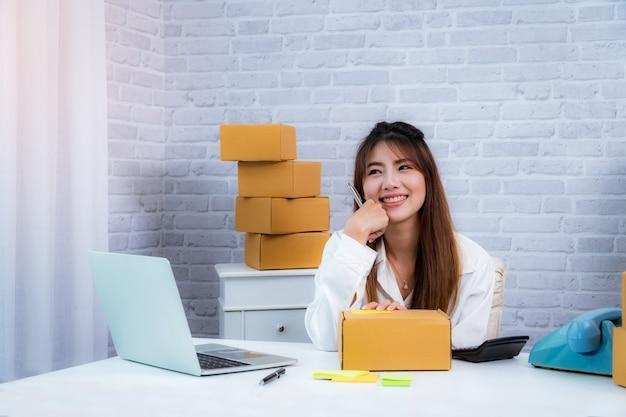 Владелец малого бизнеса женщин работая дома с коробкой упаковки на рабочем месте