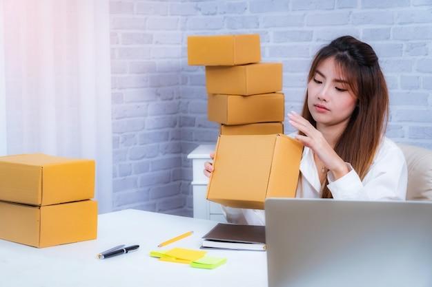 背景にホームオフィスの包装で働く若い女性事業主