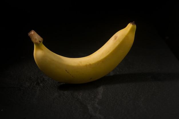新鮮な黄色のバナナは黒の背景においしい分離です。