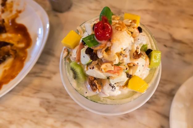 テーブルの上のカップにおいしい新鮮なフルーツサラダ