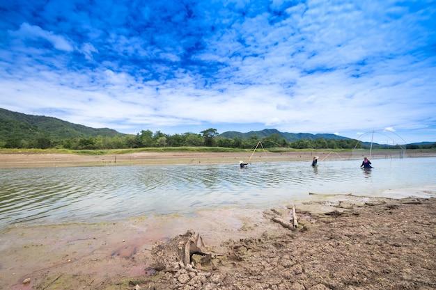 干ばつのため漁師は釣りをすることができません。乾燥した地球の温暖化のため、乾燥した割れた地面の土地