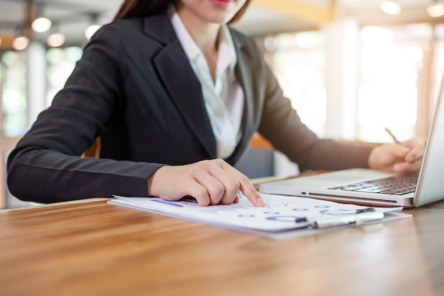 オフィスで財務報告書とラップトップコンピュータを使用して仕事をしている女性。