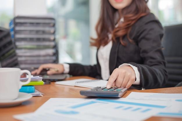 計算機を使用して書き込みとメモを作るビジネスの女性。