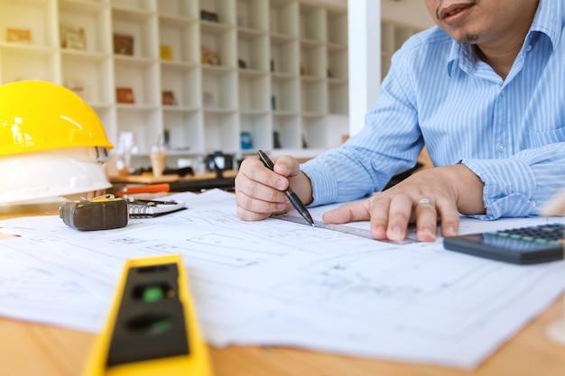 Инженер-человек, работающий в офисе, чертеж строительного проекта.