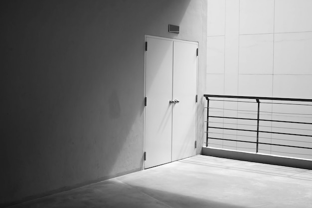 ショッピングモールの角からの光とコンクリートの壁とドア