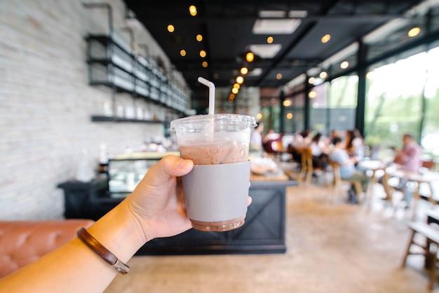 プラスチックカップにココア飲料を持っている手のクローズアップ