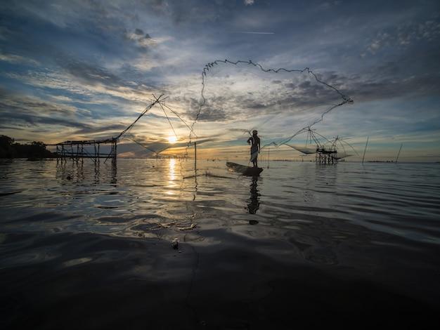 漁網を投げて漁師は水のしぶきを引き起こす魚を捕まえる