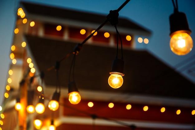 夜の結婚式のイベントに掛かっている暖かい電球と紐