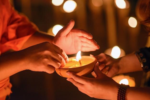 暗闇の中にキャンドルカップを持っている仏教の僧侶の手、チェンマイ、タイ