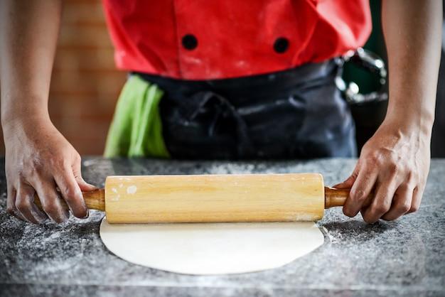 料理人がボードに生地を出す