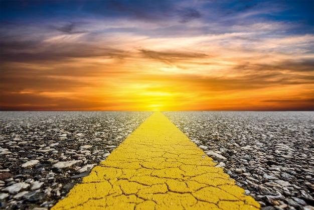 夕焼け空と太陽光線の背景が付いている道に沿って