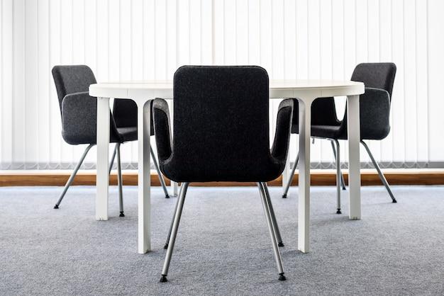 モダンなデスクと黒い椅子と空の白い事務室インテリア