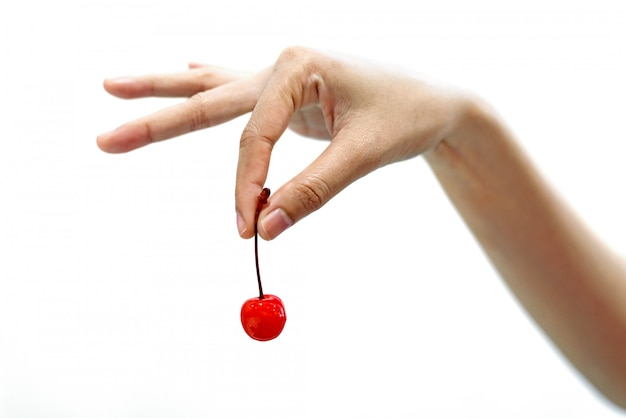 白い背景で隔離赤いチェリーフルーツを持つ女性の手