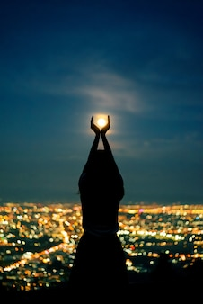 Силуэт женский портрет с полной луной в городе ночной свет боке