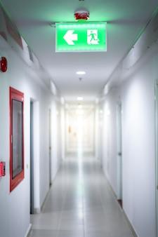 ファイアー出口緑の光のサインとドアの部屋
