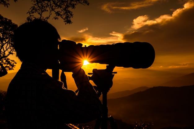 風景写真家のシルエットは夕焼け空の間に山の頂上で超望遠レンズを使用します