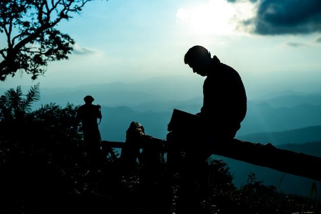 座っていると青い山のピークで本を読んで男のシルエット