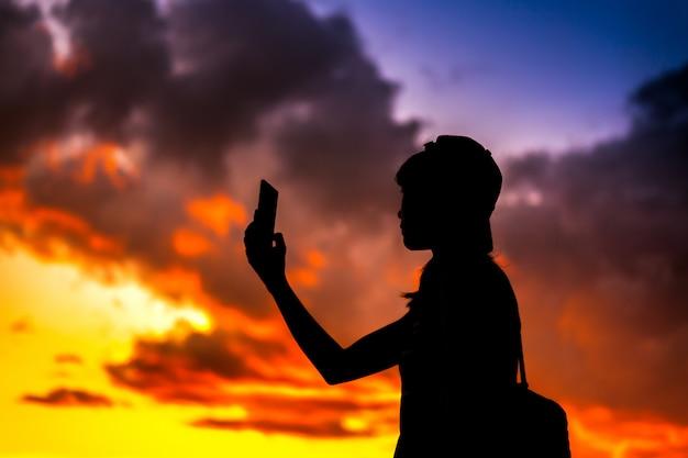 劇的な夕焼け空の背景で写真を撮る携帯電話を保持している観光客の女性のシルエット