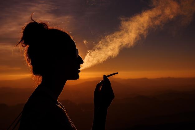 日没の風景の中の喫煙女性のシルエット