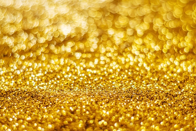 キラキラ光の抽象的なゴールドのボケ味がぼやけて背景