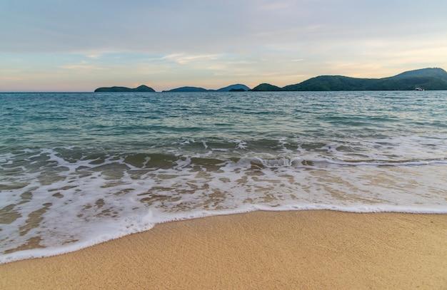 夕日の光の中で雲の空のカラフルなビーチの夕日や日の出