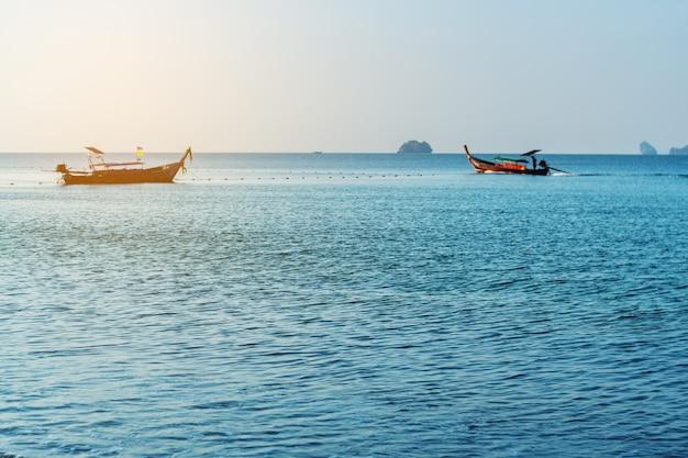 海の日の出や朝の光の中で漁船と夕日