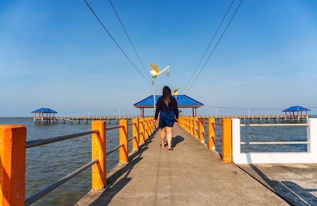 青い海の橋の上を歩く人
