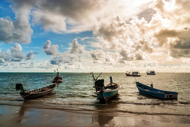 海の夕日や日の出と漁船とカラフルな空と日光の雲
