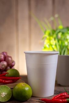 ライムとチリと玉ねぎと野菜の木製テーブルの上の麺のカップ