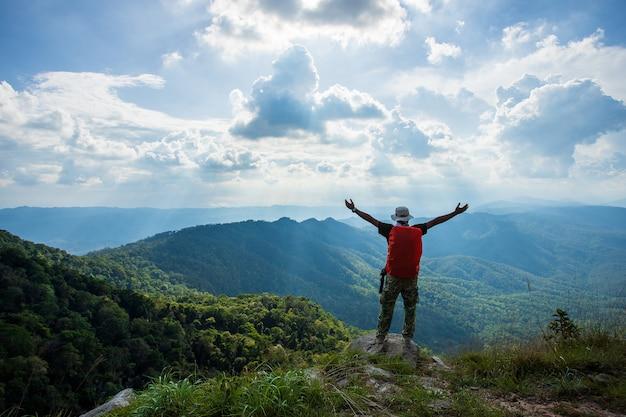 男のシルエットは山、成功の概念のピークに手を握る
