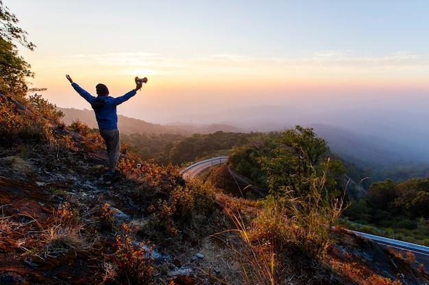 男のシルエットは山の頂上に手を握る