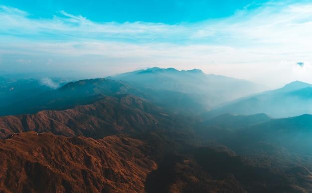 ミャンマーのムライト山に覆われた朝日と霧の黄金の光