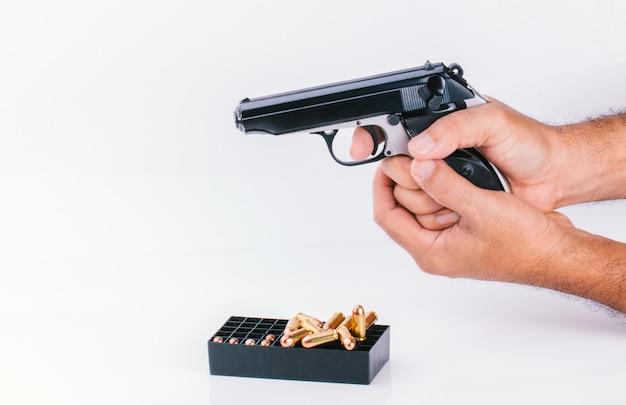 Рука с пистолетом, изолированная на белой стене