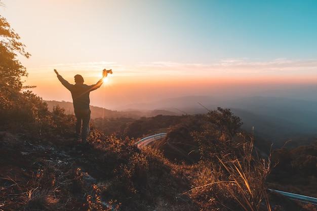 Силуэт человека задержать руки на вершине горы, концепция успеха