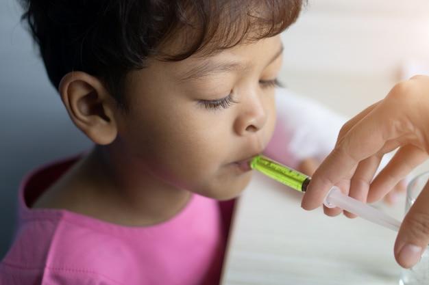 病気のアジアの子供はプラスチック注射器から薬を食べる