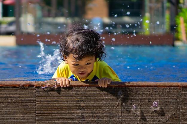 アジアの子供男の子がプールで泳ぐことを学ぶ