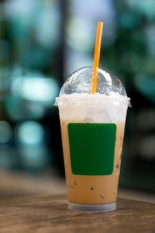 テイクアウトモックアップテンプレート用のプラスチック製のコップでカプチーノアイスコーヒー