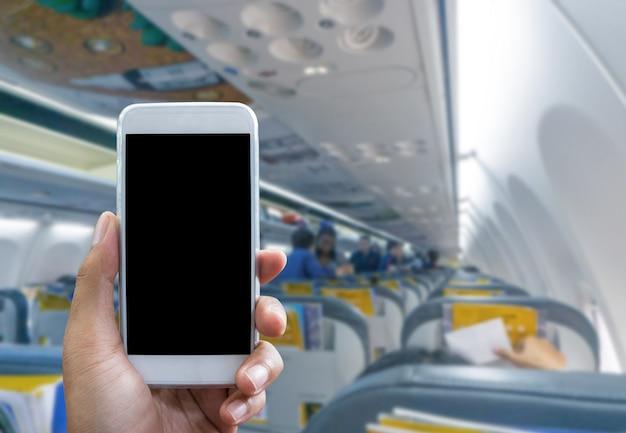 男は飛行機であなたの携帯電話を使用する背景をぼかした写真