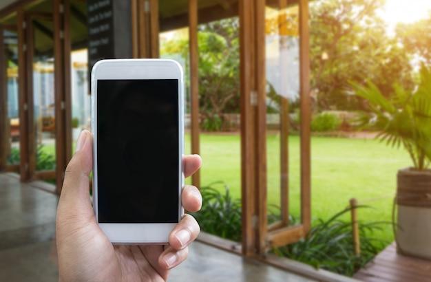 男の手は、垂直位置でモバイルスマートフォンを示しています