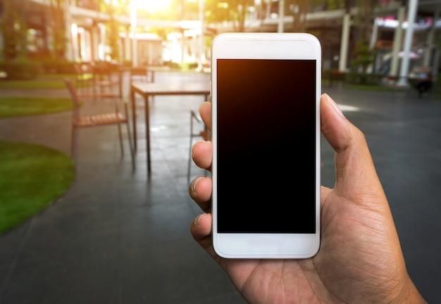 Мужская рука показывает мобильный смартфон в вертикальном положении, размыты