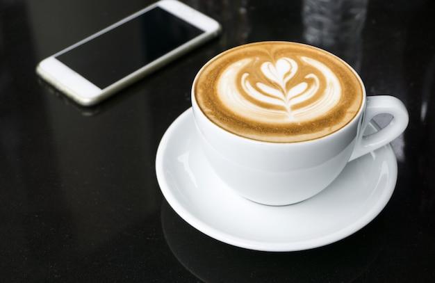 黒いテーブルの上のラテアートコーヒーのカップ