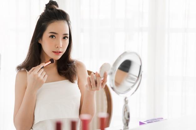 Усмехаясь молодая красивая азиатская женщина свежая здоровая кожа держа щетки состава при косметики установленные дома. лицевая концепция красоты и косметики