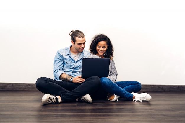 幸せな笑顔のカップルに座ってリラックスして作業し、白い壁の壁にラップトップコンピューターの技術を一緒に使用します。