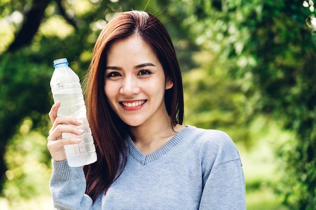 美しいアジアの女性は、リラックスして夏の緑豊かな公園の緑の自然な壁に新鮮な気分をしながらボトルから水を飲む。健康的なライフスタイルのコンセプト