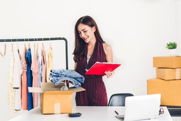 Фрилансер молодой женщины, работающий в сфере бизнеса, интернет-магазины и упаковка одежды с картонной коробкой на дому - бизнес-концепция доставки и доставки онлайн