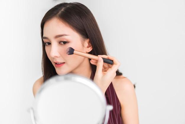 Усмехаясь кожа молодой красивой азиатской женщины свежая здоровая смотря на зеркале и держа щетки состава на дому. лицевая концепция красоты и косметики