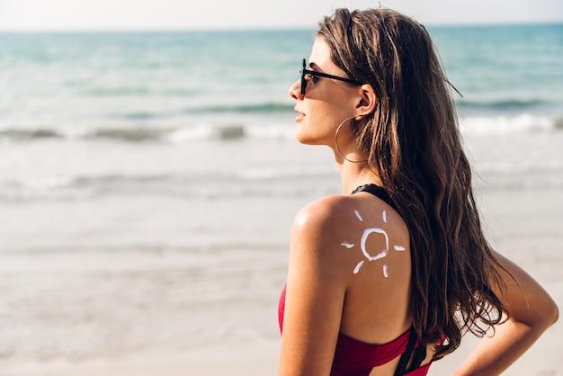 Женщина в бикини из двух частей, применяя крем с солнцем на спине на тропическом пляже. летний отдых