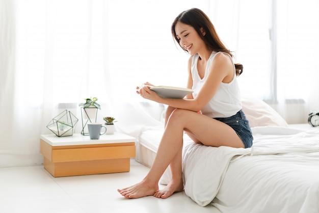 本を読んでリラックスして、自宅のベッドでホットコーヒーや紅茶のカップを飲む若い女性